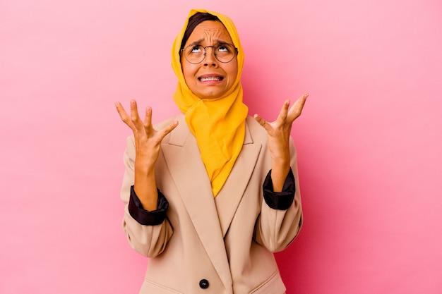空に向かって叫び、見上げて、欲求不満のピンクの背景に孤立した若いビジネスイスラム教徒の女性。