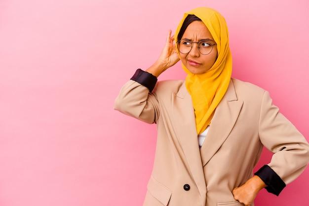 Молодая деловая мусульманская женщина изолирована на розовом фоне, касаясь затылка, думая и делая выбор.