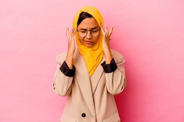 こめかみに触れて頭痛を持っているピンクの背景で隔離の若いビジネスイスラム教徒の女性。