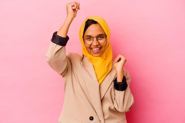 特別な日を祝うピンクの壁に孤立した若いビジネスイスラム教徒の女性は、エネルギーでジャンプして腕を上げる