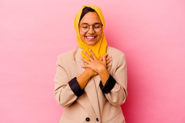 ピンクの壁に孤立した若いビジネスイスラム教徒の女性は、心に手を置いて笑って、幸せの概念。