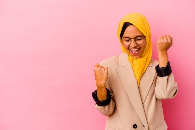 勝利の後に拳を上げるピンクの壁に孤立した若いビジネスイスラム教徒の女性