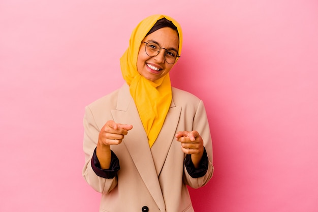 Young business muslim woman isolated on pink background cheerful smiles pointing to front.