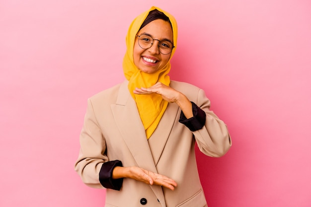 Young business muslim woman isolated on pink background holding something with both hands, product presentation.