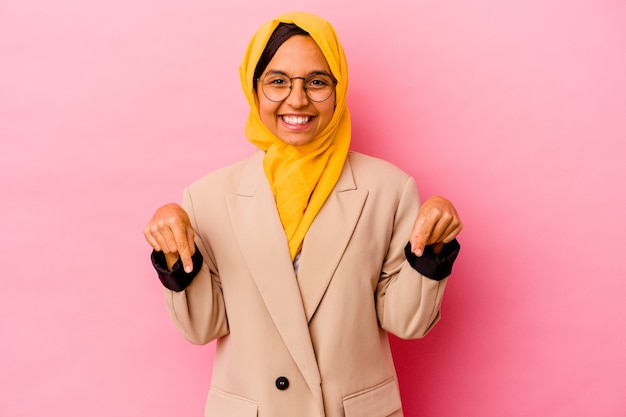 Young business muslim woman isolated on pink background points down with fingers, positive feeling.