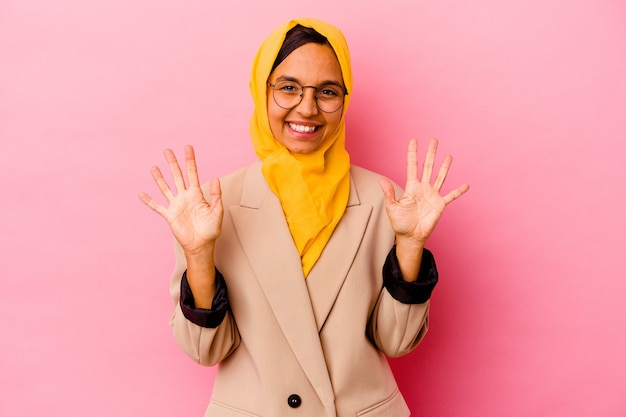 Young business muslim woman isolated on pink background showing number ten with hands.