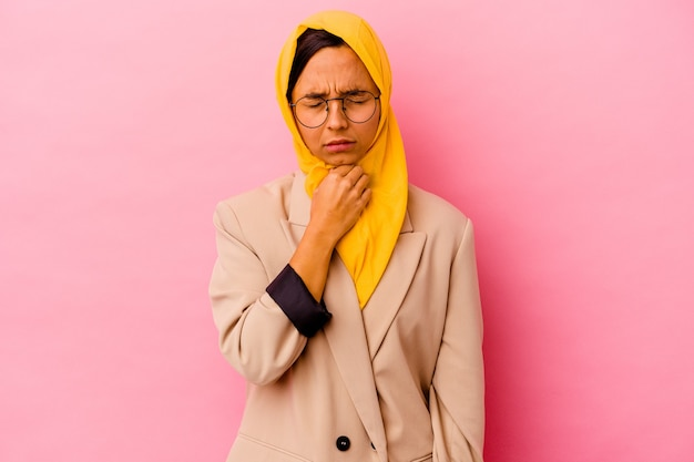 Young business muslim woman isolated on pink background suffers pain in throat due a virus or infection.