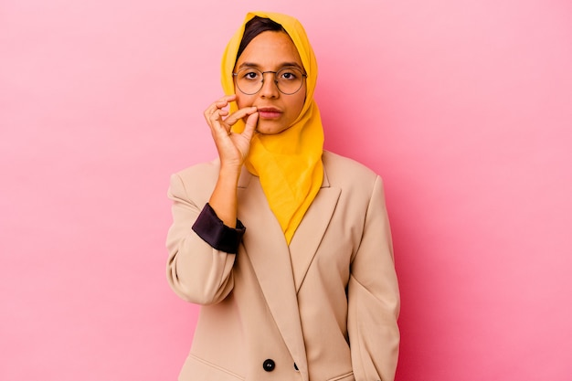 Young business muslim woman isolated on pink background with fingers on lips keeping a secret.