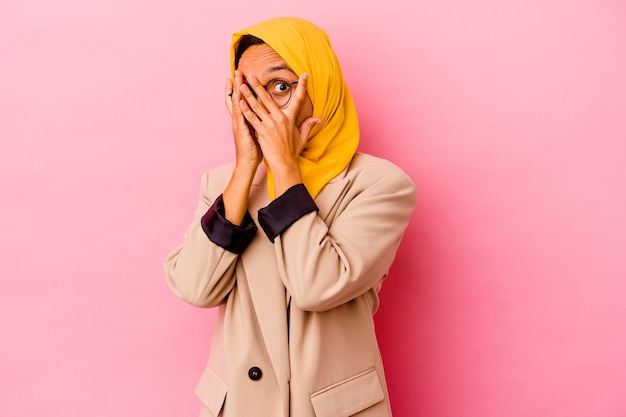 Young business muslim woman isolated on pink wall blink through fingers frightened and nervous.