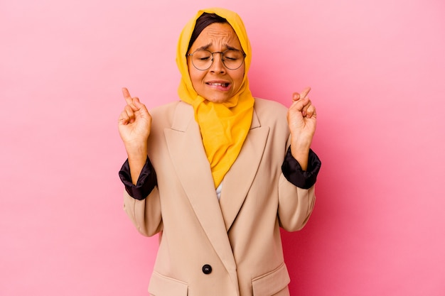 Young business muslim woman isolated on pink wall crossing fingers for having luck