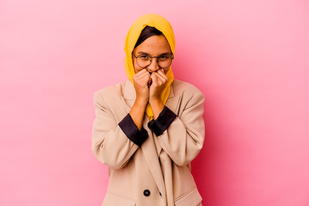 Young business muslim woman isolated on pink wall laughing about something, covering mouth with hands.
