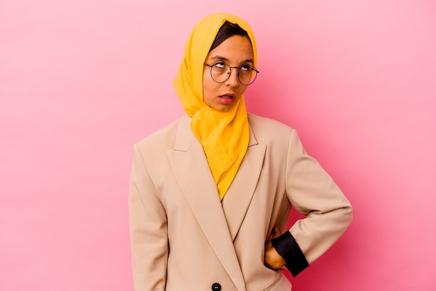 Young business muslim woman isolated on pink wall tired of a repetitive task