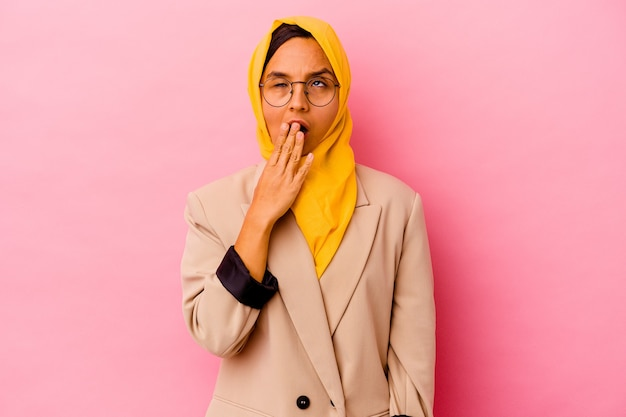 Young business muslim woman isolated on pink wall yawning showing a tired gesture covering mouth with hand