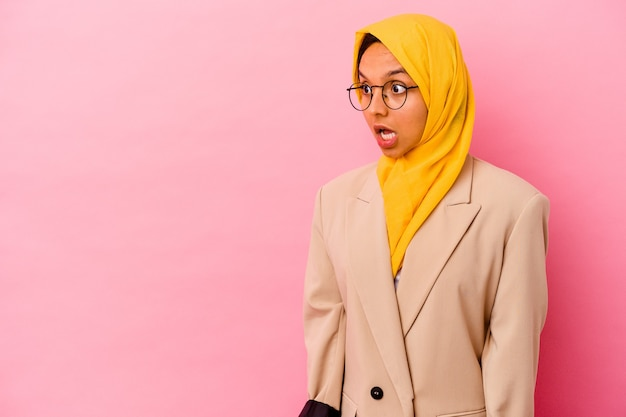 Young business muslim woman on pink being shocked because of something she has seen.