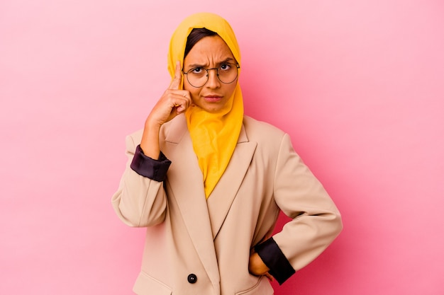 Young business muslim woman on pink pointing temple with finger, thinking, focused on a task.