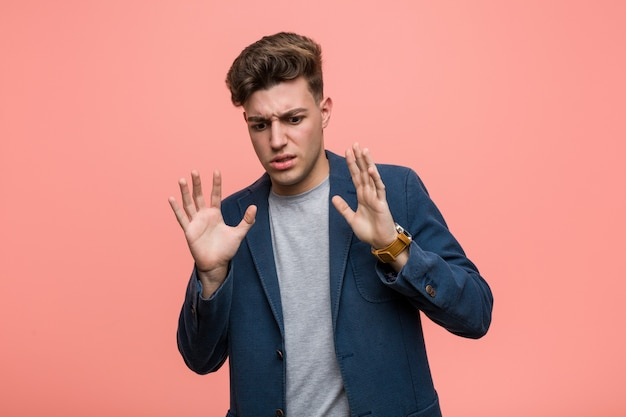 Young business natural man rejecting someone showing a gesture of disgust.