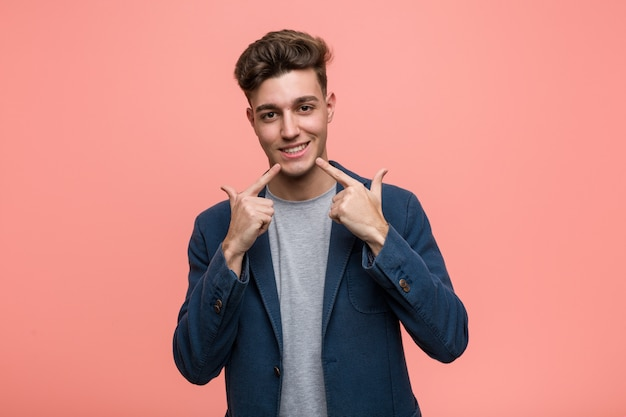 Young business natural man smiles, pointing fingers at mouth.