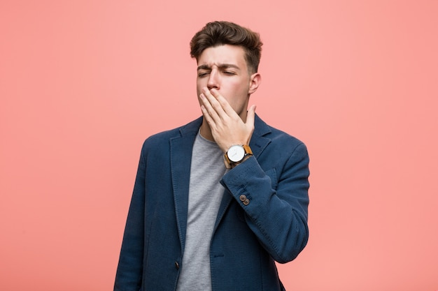 Young business natural man yawning showing a tired gesture covering mouth with him hand.