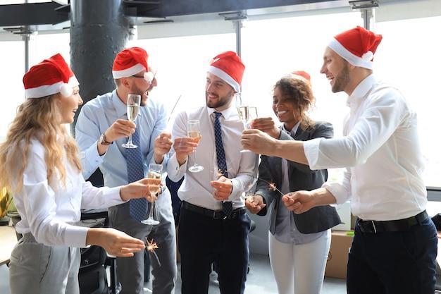 若いビジネスパートナーは、現代のオフィスでベンガルライトを点灯し、シャンパンを飲んでいます。メリークリスマス、そしてハッピーニューイヤー。