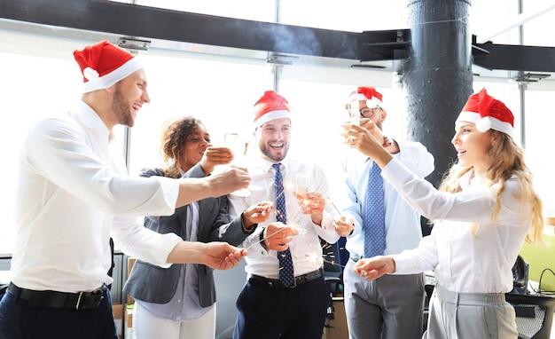 Молодые деловые партнеры зажигают бенгальские огни и пьют шампанское в современном офисе. веселого рождества и счастливого нового года.