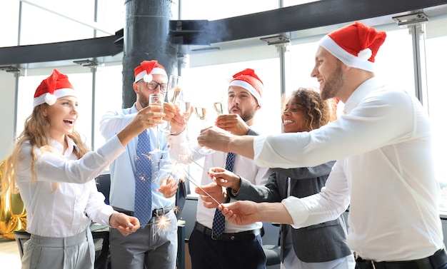 Young business partners are lighting bengal lights and drinking champagne in a modern office. merry christmas and happy new year.