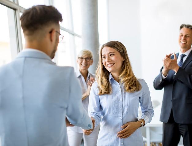 彼らのチームがバックグラウンドで拍手している間、オフィスで握手をする若いビジネスパートナー