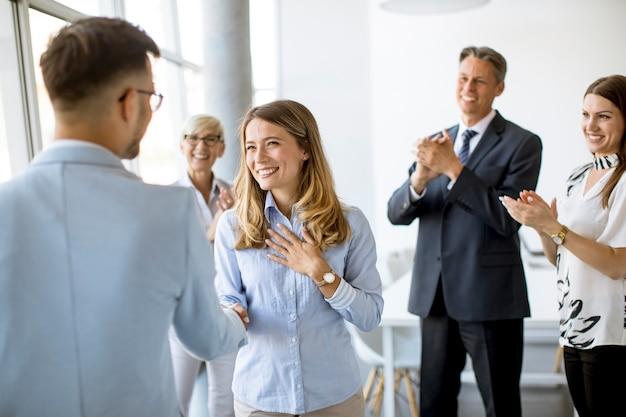 Молодые деловые партнеры пожимают друг другу руки в офисе, пока их команда аплодирует
