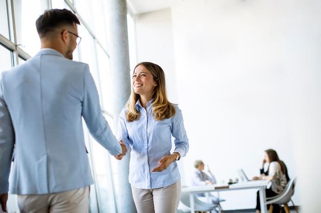 彼らのチームがバックグラウンドで作業しながらオフィスで握手をする若いビジネスパートナー