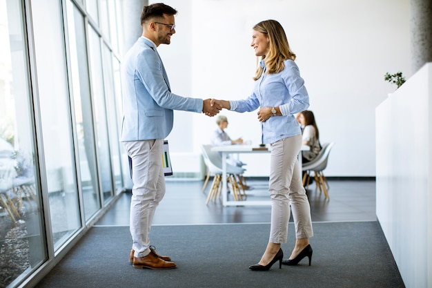 Young business partners making handshake in an office while their team working in the background