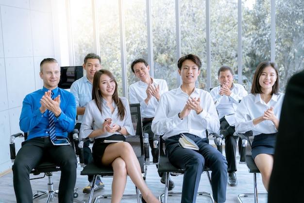 Молодым деловым людям в офисе конференц-зала представлен проект маркетинговой работы заказчику.