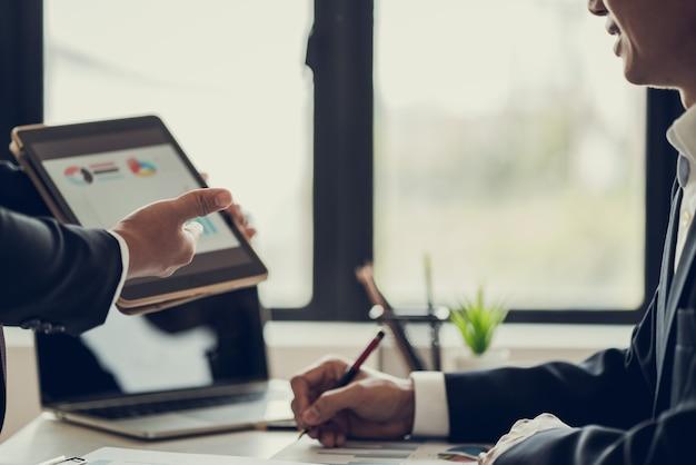 Молодые деловые люди представляют заказчику маркетинговый рабочий проект в офисе для переговоров.