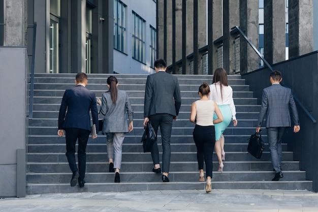 휴식에서 돌아 오는 젊은 비즈니스 사람들 동료. 정장을 입은 남녀가 사무실 건물로 계단을 올라갑니다. 파트너십, 커뮤니케이션 비즈니스 사람들이 개념.