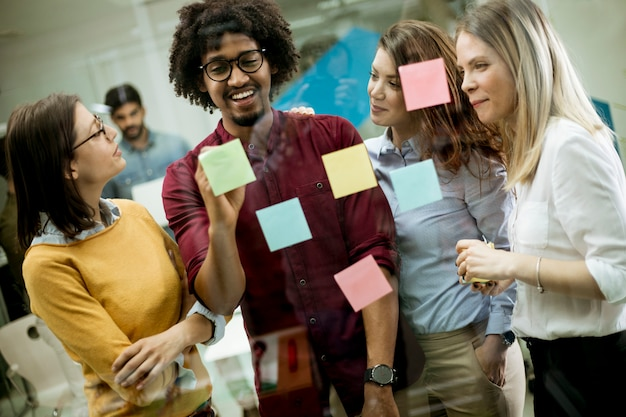 ポスト・イットノートとステッカーを使用してガラスの壁の前で議論する若いビジネス人々