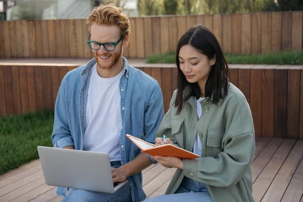 屋外で一緒に働くラップトップを使用して会う若いビジネスマン