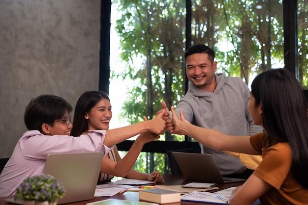 若いビジネスの人々が一緒に触れて大きな打撃に達します。幸せな気持ちで。同僚のチームミーティング、成功取引