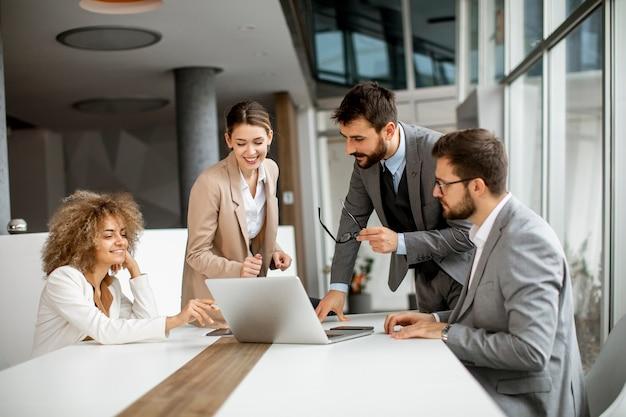 Молодые деловые люди сидят за столом для переговоров в конференц-зале, обсуждают стратегию работы и планирования