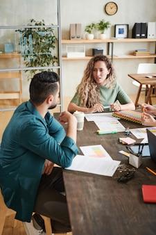 Молодые деловые люди сидят за столом с документами и обсуждают финансовый отчет в команде во время встречи в офисе