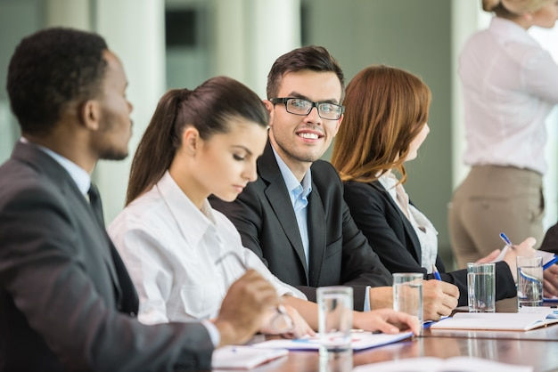 Young business people in suits sitting at meeting room.