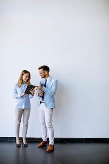 Молодые деловые люди с цифровым планшетом у стены в офисе