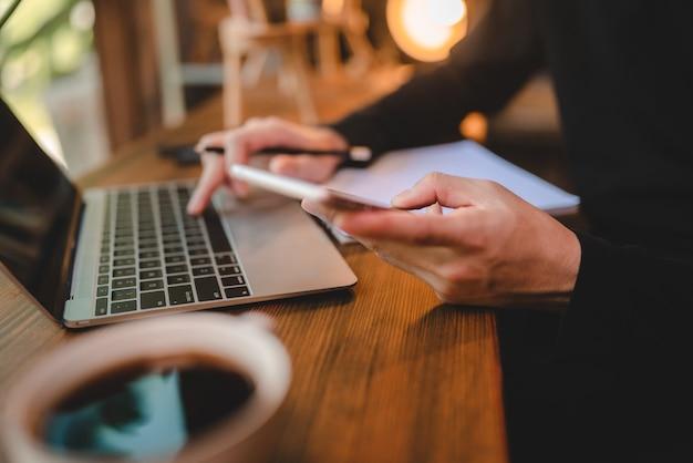 コンピューターのラップトップ技術を使用してカフェの共同作業スペースで働く若いビジネスマン、オンラインサイバースペース通信オンラインオフィスを介して現代のライフスタイルを持つプロの労働者
