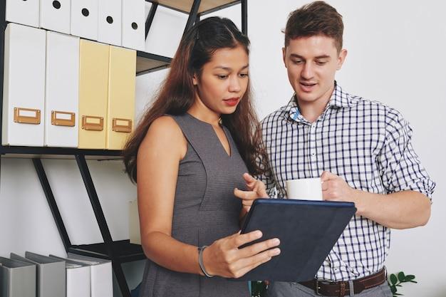 사무실에서 일하고 태블릿 컴퓨터에 대한 정보를 논의하는 젊은 비즈니스 사람들