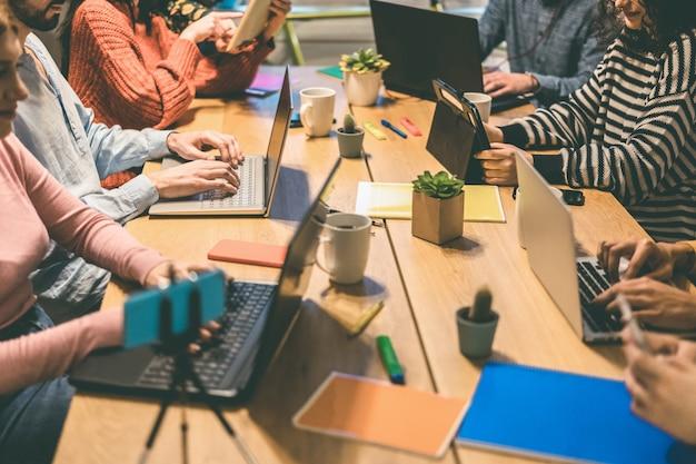 Молодые деловые люди, работающие в современном коворкинг-офисе - сосредоточьтесь на руках человека в центре