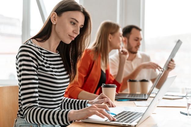 Молодые деловые люди, работающие на ноутбуке