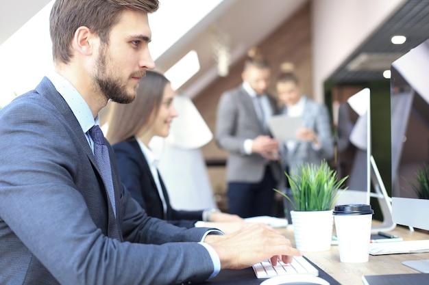 Молодые деловые люди, работающие на своих настольных компьютерах в современном офисе.