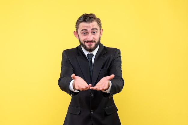 Giovane uomo d'affari che riceve una piacevole sorpresa che mostra le mani alzate