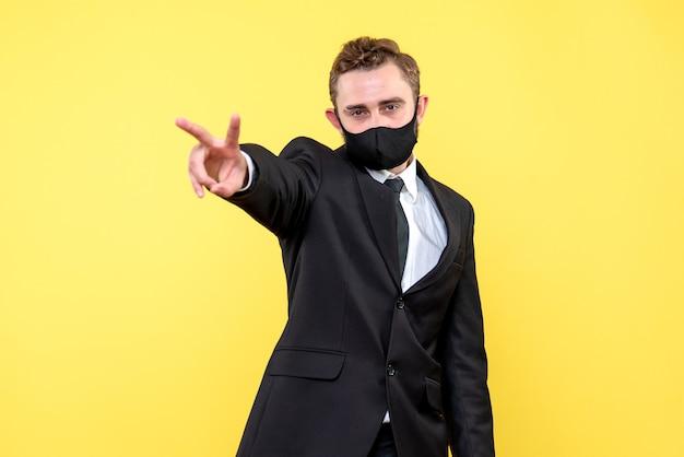 Молодой деловой человек показывает знак победы на желтом