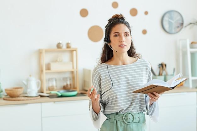 집에서 시간을 보내는 동안 온라인 회의 기술을 사용하여 그녀의 팀과 이야기하는 젊은 비즈니스 사람