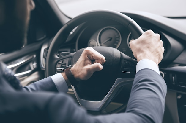Young business person test drive new vehicle push beep