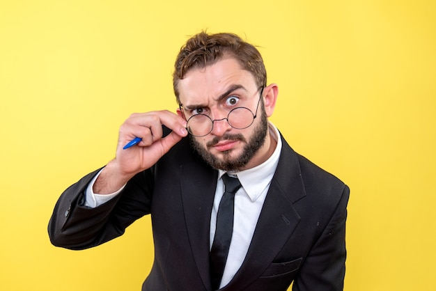 Young business person with glasses focused on one point over yellow