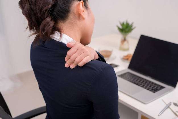 Young business person with neck pain. focus on hand on neck with laptop on table in background.